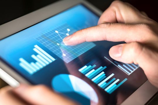 Business figures, graphs, chart and statistics. Market or economic report for financial analysis. Man working and using tablet. Finger touching screen. Entrepreneur making budget or strategy.