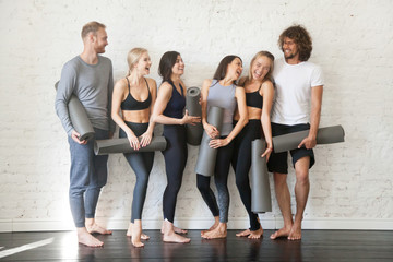 Group portrait of young sporty excited people with exercise mats standing beside white wall joking and laughing together. Candid funny students taking rest from fitness activity. Full length photo