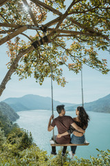 couple enjoying nature from a hill top sitting on a swing