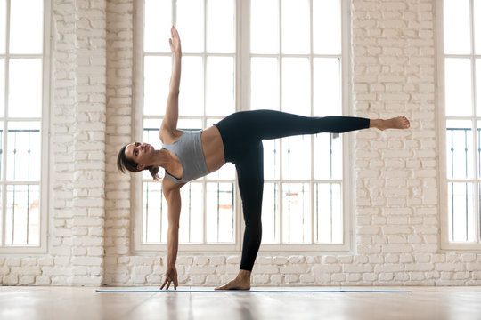 Young sporty yogi woman practicing yoga, doing Half Moon exercise, Ardha Chandrasana pose, working out, wearing sportswear, pants and top, indoor full length, white yoga studio
