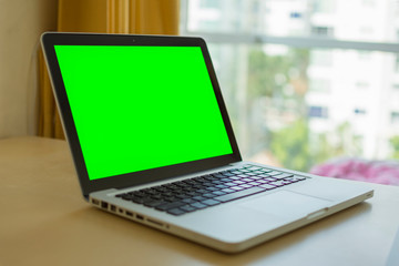 Laptop with green screen for replacement with blur background