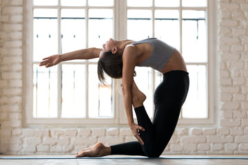 Young sporty yogi woman practicing yoga, doing Ustrasana exercise, Camel pose, working out, wearing sportswear, black pants and top, indoor full length, white yoga studio