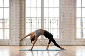Young sporty attractive woman practicing yoga, doing Wild Thing, Flip-the-Dog exercise, Camatkarasana pose, working out, wearing sportswear, black pants and top, indoor full length, white yoga studio