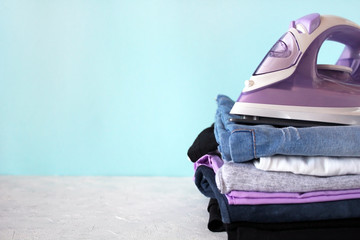 Pile of colorful clothes and violet electric iron on blue background. Household domestic work, homework concept.