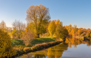 Color outdoor fall nature image of a rural autumnal river scene with blue sky, colorful trees reflecting on the water, a bench and a path along the riverside on a bright sunny day