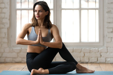 Young attractive woman practicing yoga, doing Half lord of the fishes exercise, Ardha Matsyendrasana pose with namaste , working out, wearing sportswear, pants and top, indoor full length, yoga studio