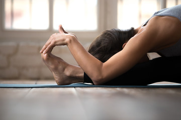 Young sporty attractive woman practicing yoga, doing paschimottanasana exercise, Seated forward bend pose, working out, wearing sportswear, black pants and top, indoor close up, white yoga studio