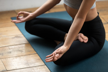 Young sporty yogi woman practicing yoga on blue mat, doing Padmasana exercise, Lotus pose with mudra gesture, working out, wearing sportswear pants, indoor close up, yoga studio. Well-being concept