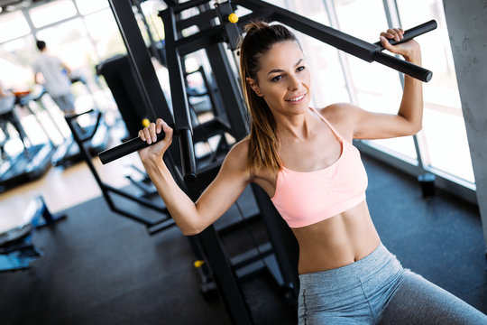 Happy woman exercising on a shoulder press in fitness center