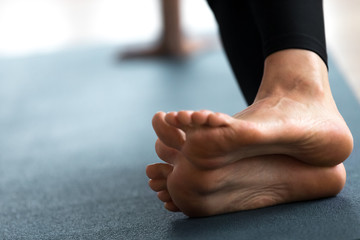 Young sporty woman practicing yoga, doing strengthening exercises, healing physical therapy pose, working out, indoor close up, yoga studio, focus on feet. Foot and heel care, fitness concept