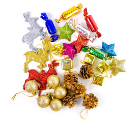 Christmas toys of decor balls, beads,candies, reindeer red pink blue golden decorations on white background. Top view.