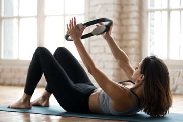 Young sporty attractive woman doing toning pilates exercise for abs with fitness circle, crunches for abdominal strength using pilates magic circle, wearing sportswear at yoga studio or at home