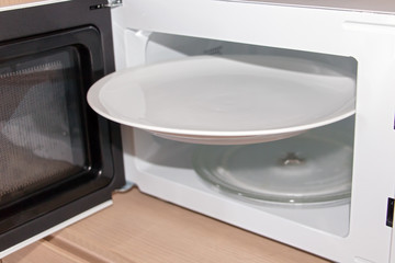 an open microwave with a white plate. An empty large disc is wedged in a microwave oven.