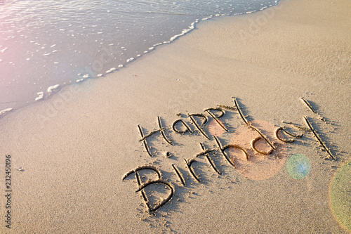 Happy Birthday Message Handwritten In Smooth Sand With Festive Lens Flare On The Shore Of