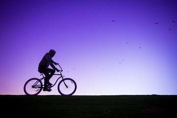 Poster Cycling Silhouette of man in hoodie riding a beach cruiser bicycle against a glowing purple sky