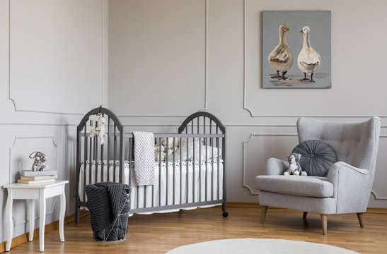 Stylish grey baby room with wooden crib, comfortable armchair and white table with books, real photo with copy space on the empty wall