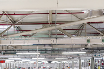interior of a large industrial workshop, luminescent lamps under the ceiling are suspended in rows. Working atmosphere.