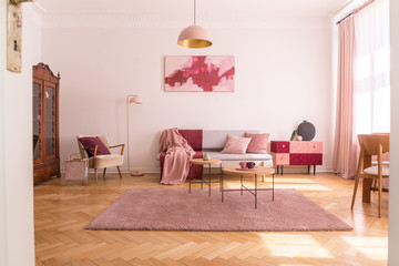 Trendy living room interior with grey couch with pastel pink pillows and blanket, stylish beige armchair with burgundy pillow and retro cabinet in the corner