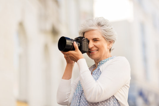 old age, photography and people concept - happy senior woman photographing by digital camera on city street