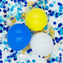 drei Luftballons mit blauem Konfetti, gelben Luftschlangen