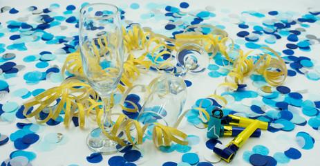 Hintergrund aus blauem Konfetti, gelben Luftschlangen und Sektgläsern