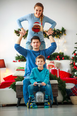Family with boy having fun playing at home in Christmas decorations