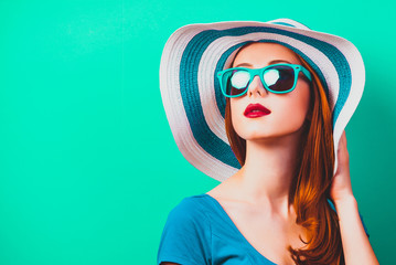 style redhead girl with makeup in blue hat and sunglasses on green background isolaed Wall mural