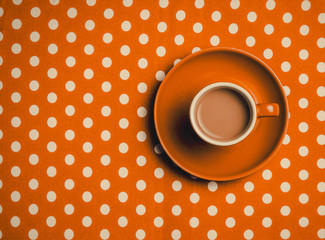 orange cup of coffee with milk on polka dot background. Above view