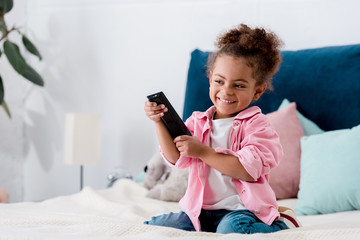 Smiling curly African american kid sitting on the bed with tv remote