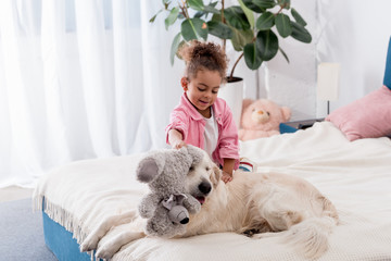 Cute african american kid sitting on the bed and playing with teddy bear and retriever