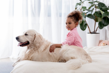 Adorable african american kid hugs her dog on the bed