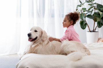 Adorable african american kid sitting on the bed on the side of her golden retriever