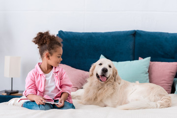 Curly african american kid sitting on the bed with smartphone and smiling golden retriever