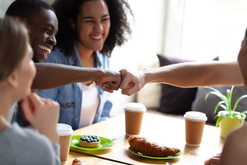 Happy multiracial students girls and guys laughing sitting in cafe celebrating successfully passed exams. Mixed race best friends greeting together fist bumping symbol of giving respect and friendship