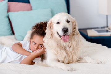 little frowned african american kid lying on bed while leaning to dog