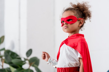 Portrait of cute little african american child in  red superhero costume and mask