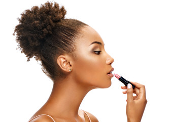 Beautiful girl applying lipstick on her lips. Photo of african american girl in profile on white background. Skin care and beauty