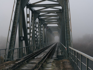 old railway bridge in the early foggy morning. terrible place