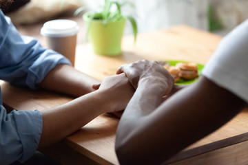 Black african guy holds hand of beloved girl, sitting together at table expressing showing her sincere feelings or apologizing saying sorry. Reliable person, trusted friend, true friendship concept