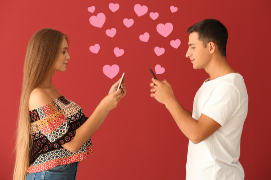 Young couple with mobile phones on red background. Online dating