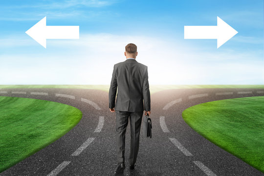 Businessman standing at crossroads with arrows. Concept of choice
