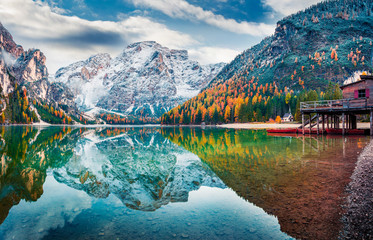 Boat hut on Braies Lake with Seekofel mount on background. Colorful autumn sunrise of Italian Alps, Naturpark Fanes-Sennes-Prags, Dolomite, Italy, Europe. Traveling concept background.