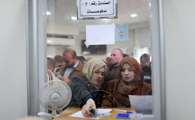 Palestinian Hamas-hired employees receive full salaries for the first time in years, in the southern Gaza Strip