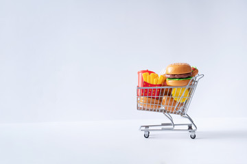 Shopping cart full with fast food items. Minimal jubk food concept.
