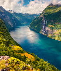 Splendid summer scene of Sunnylvsfjorden fjord, Geiranger village location, western Norway. Aerial view of famous Seven Sisters waterfalls. Beauty of nature concept background.