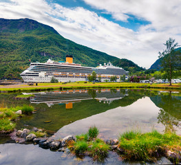 Splendid summer view of Sognefjorden fjord. Colorful morning scene of Flom port, Norway with large cruise ship. Traveling concept background. Artistic style post processed photo.
