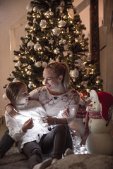 Single mother embracing daughter in front of Christmas tree - New Year's eve