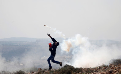 Palestinian demonstrator hurls back a tear gas canister fired by Israeli troops during a protest in the occupied West Bank