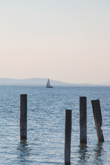 View through the wooden dock pillars standing in water to the sea horizon with small sailboat sailing near coastal hills, blue seascape with vertical lines and horizon in the middle