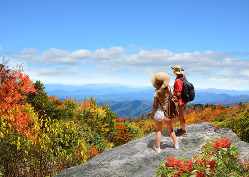 Couple on hiking trip looking at beautiful autumn mountain landscape,  Friends  relaxing on top of the mountain. Blue Ridge Parkway, Close to Blowing Rock, North Carolina,USA.